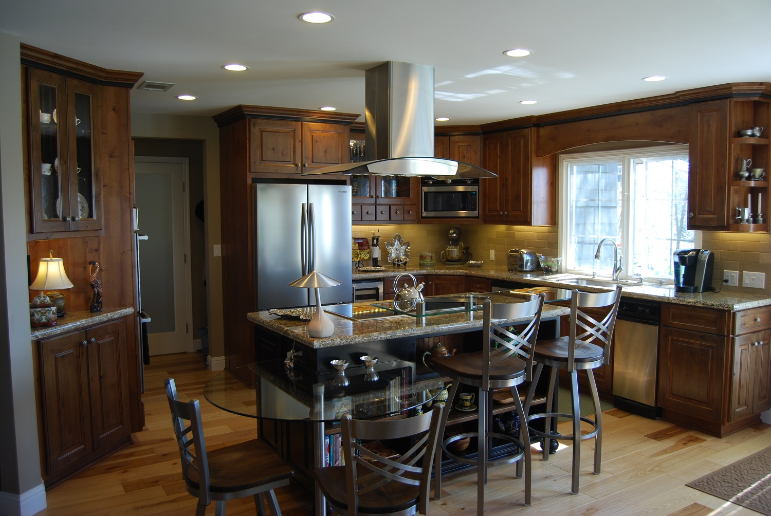 knotty hickory floors, arched glass range hood, glass counter table and bar