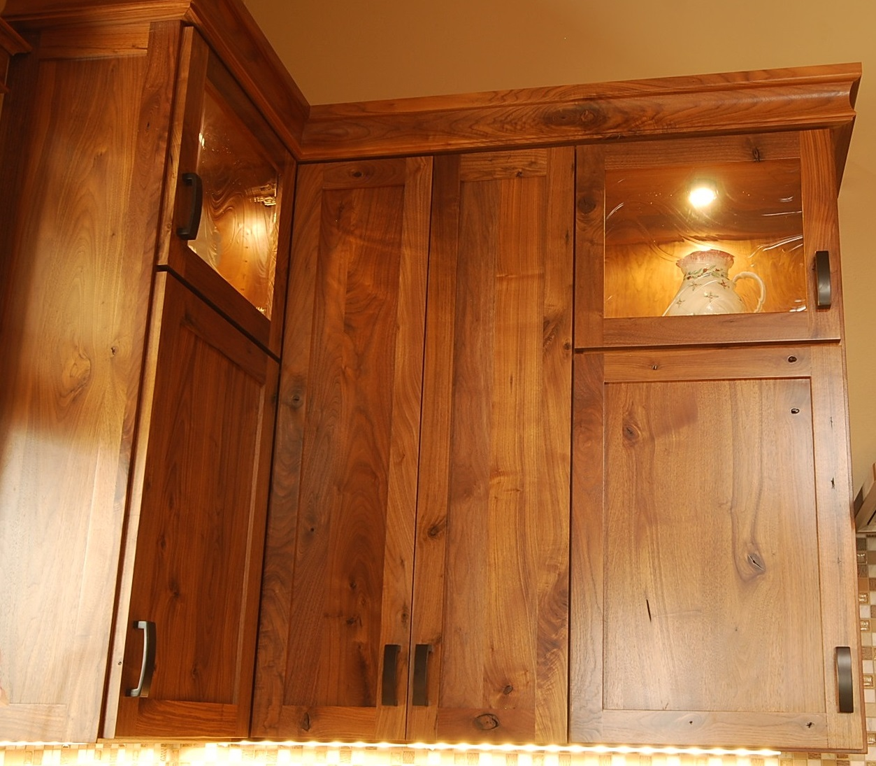 Rustic Walnut upper cabinets with antique wavy glass
