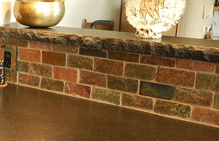 Black absolute granite counters with a chiseled edge and slate brick backsplash